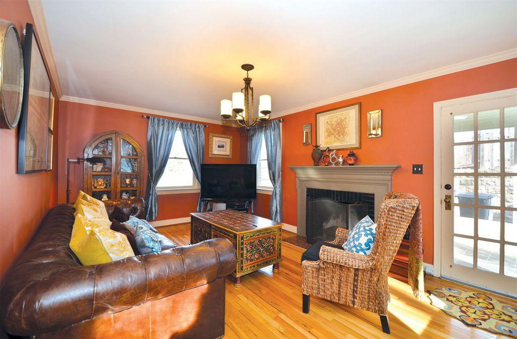 Eclectic Living Room with Hardwood floors, Crown molding, Chandelier, Cement fireplace, Built-in bookshelf, French doors