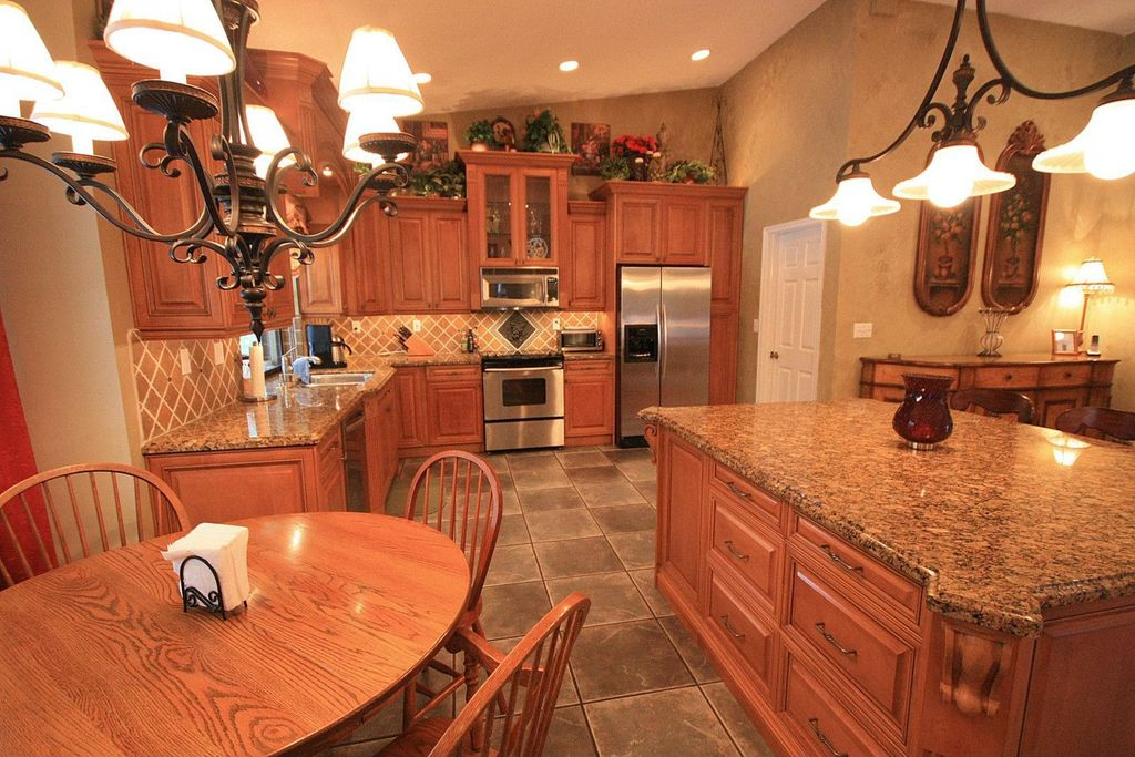 Country Kitchen with gas range, Limestone Tile, Kitchen island corbel, Pendant light, Undermount sink, L-shaped, Stone Tile