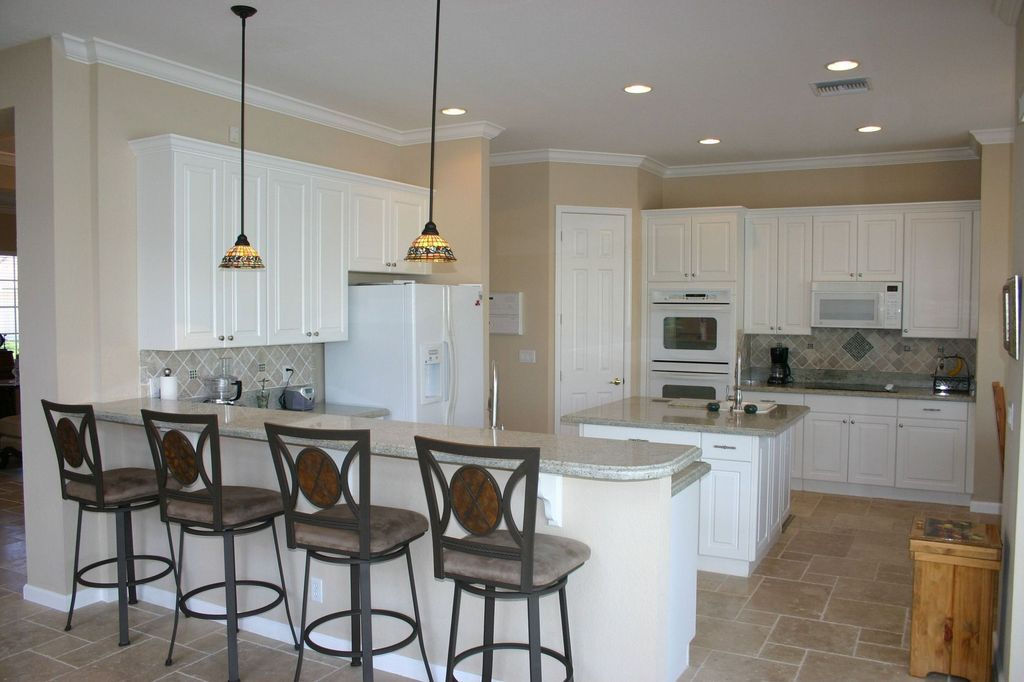 Traditional Kitchen with L-shaped, six panel door, Framed Partial Panel, drop-in sink, electric cooktop, stone tile floors
