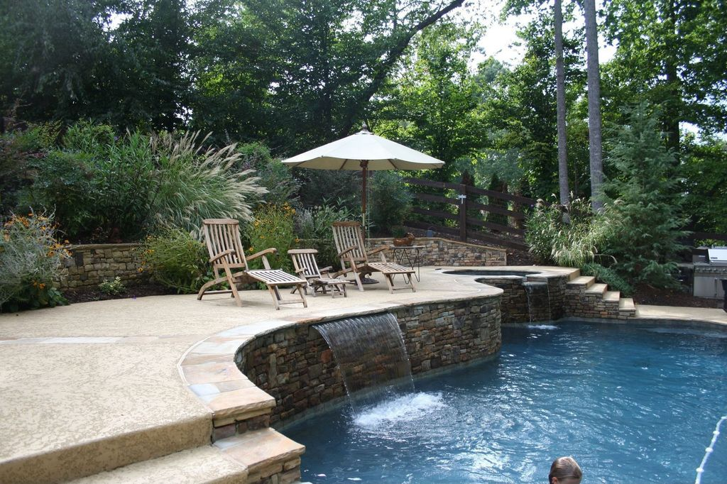 Modern Swimming Pool with Fence, Infinity pool, exterior stone floors, Outdoor kitchen
