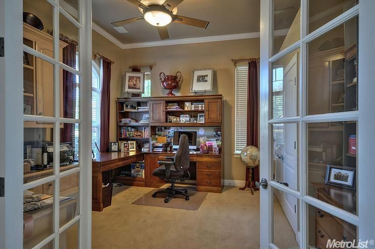 Traditional Home Office with Ceiling fan, Crown molding, specialty door, Standard height, Built-in bookshelf, Arched window