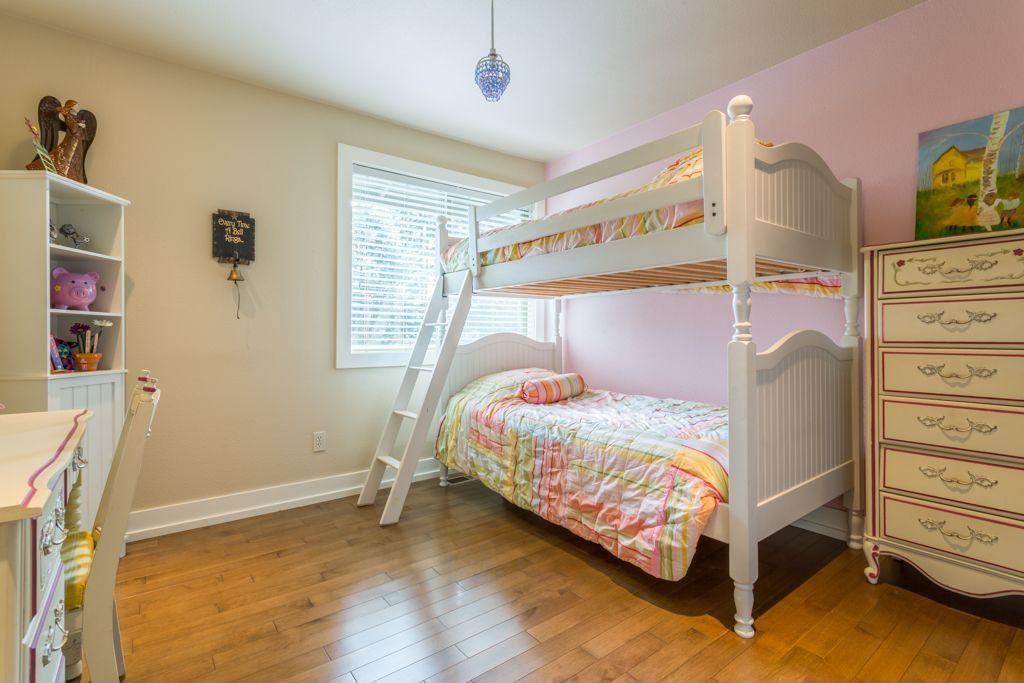 Traditional Kids Bedroom with Hardwood floors, Standard height, picture window, Pendant light, Built-in bookshelf