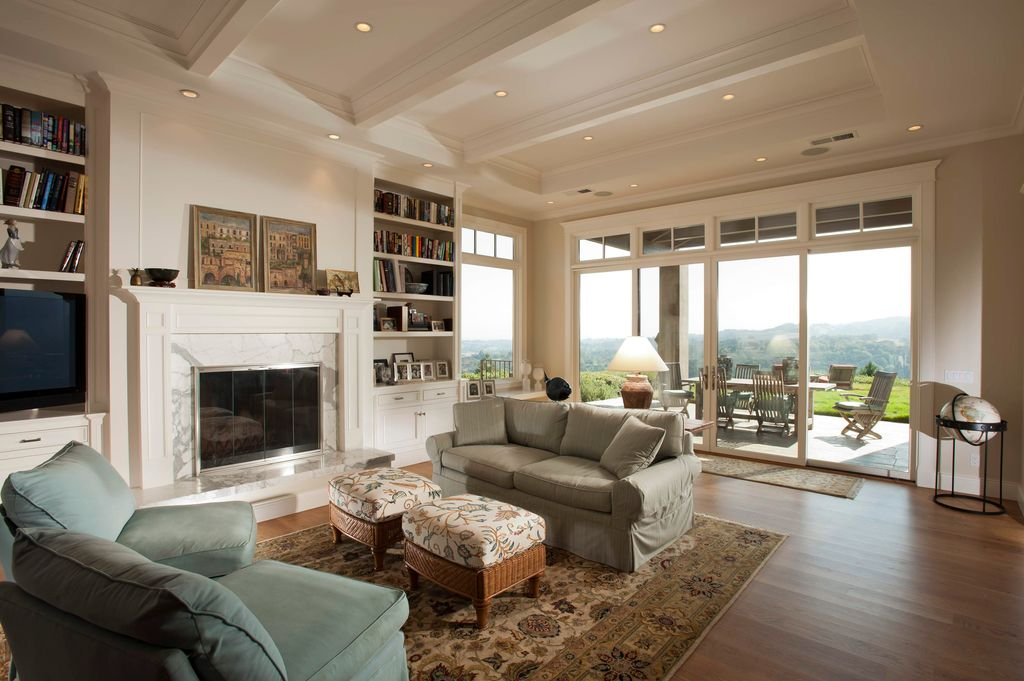 Traditional Living Room with Exposed beam, picture window, Fireplace, Floral area rug, Hardwood floors, Standard height