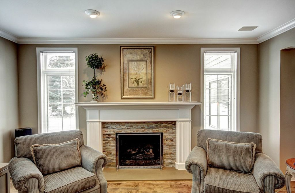Traditional Living Room with picture window, Standard height, can lights, Fireplace, Crown molding, Casement, stone fireplace
