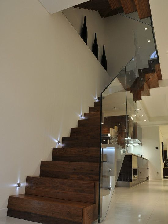 Contemporary Staircase with High ceiling, Wall sconce, Hardwood floors, curved staircase