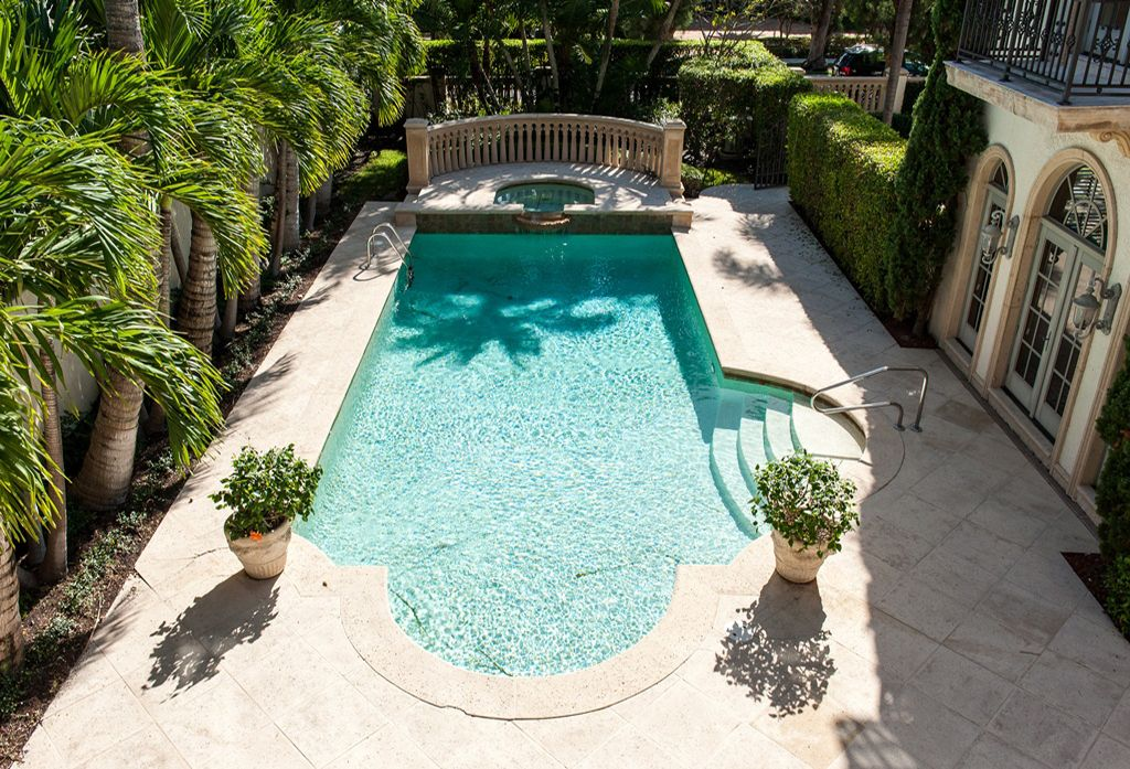Mediterranean Swimming Pool with Deck Railing, Fence, Pool with hot tub, exterior tile floors, French doors, Arched window