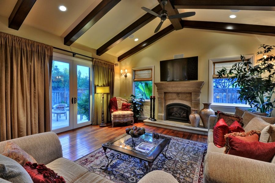 Mediterranean Living Room with High ceiling, Cement fireplace, Ceiling fan, Hardwood floors, Wall sconce, Exposed beam