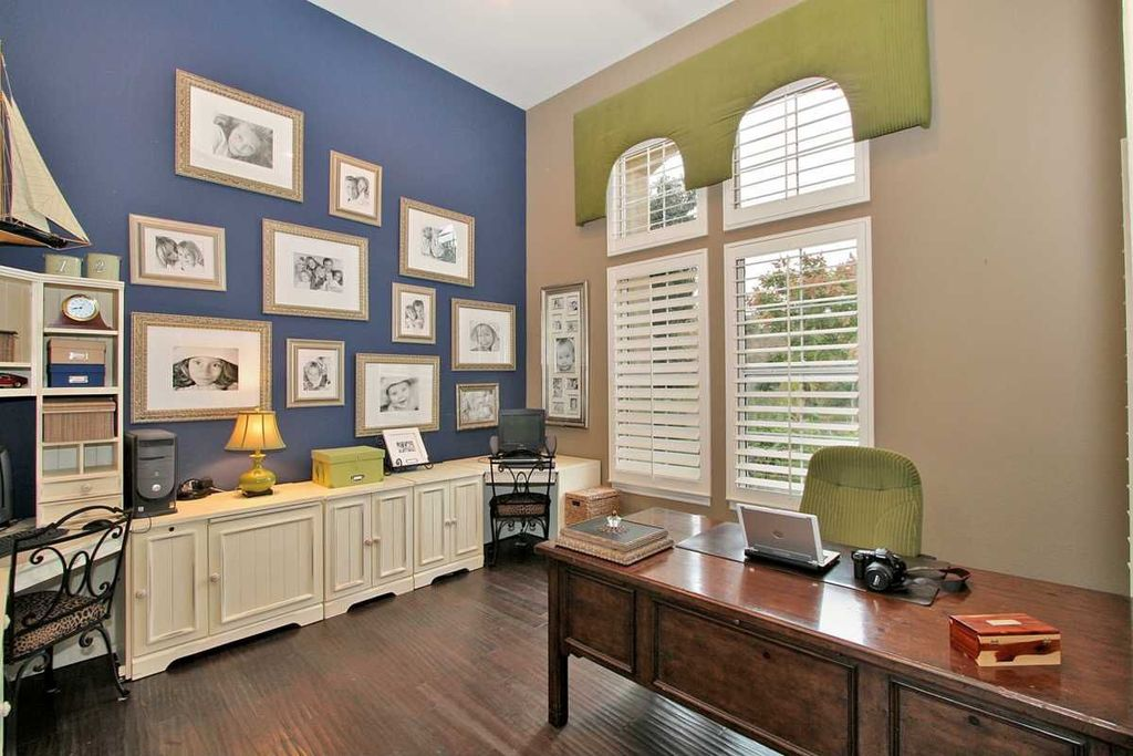 Traditional Home Office with Built-in bookshelf, Arched window, specialty window, Standard height, Laminate floors