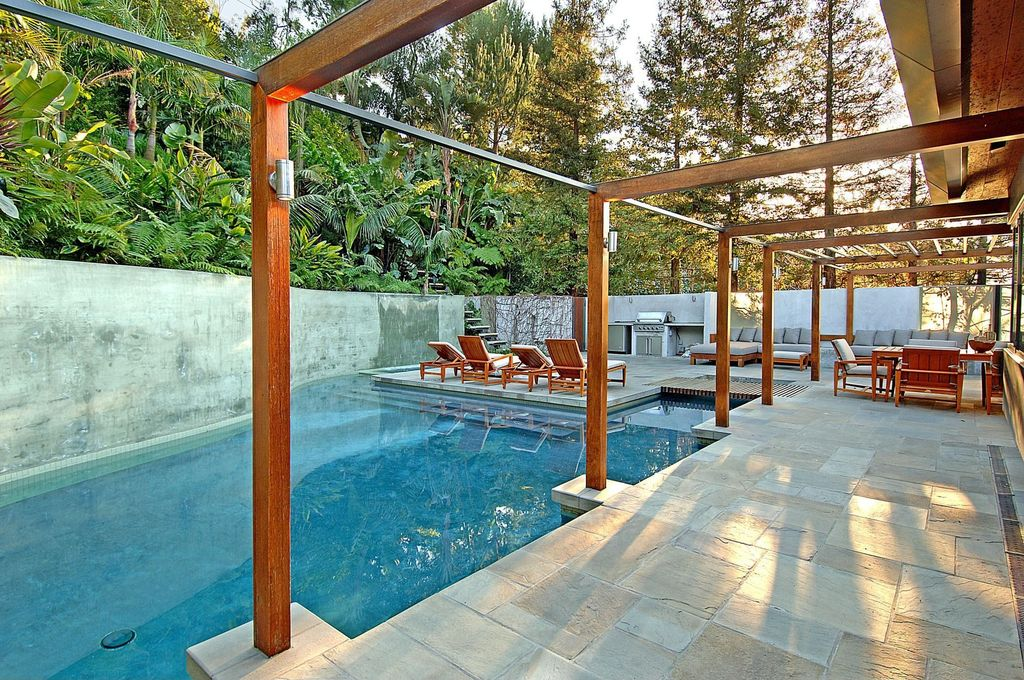 Contemporary Swimming Pool with Outdoor kitchen, exterior stone floors, Other Pool Type, Fence